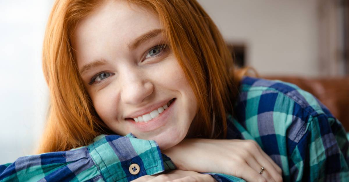 woman smiling and wearing a blue plaid shirt