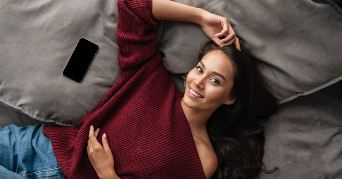 woman lying down with red asymmetrical shirt