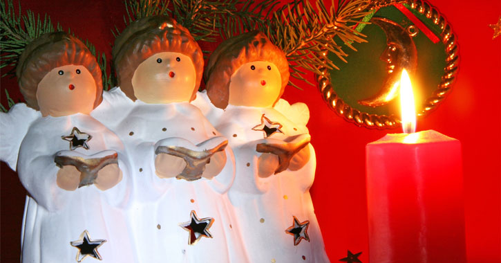 three angel figurines singing by a lit red candle
