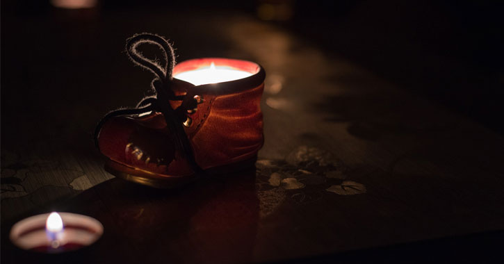 a tiny glowing shoe with a lit candle in the foreground