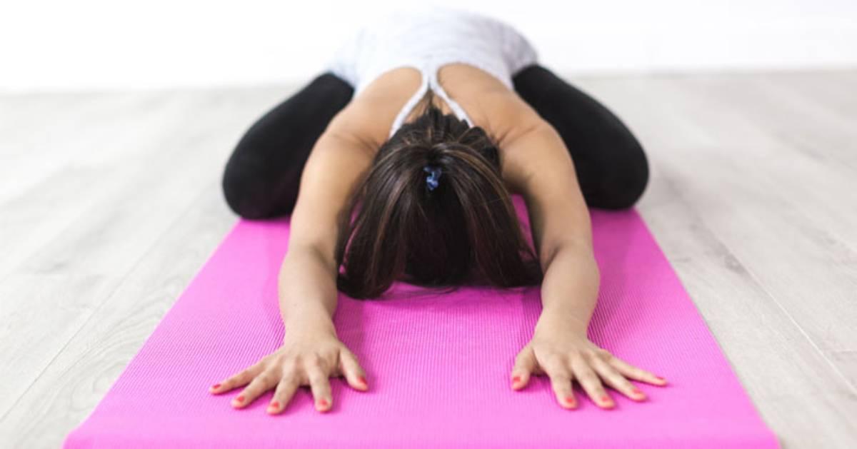 woman doing yoga on pink mat