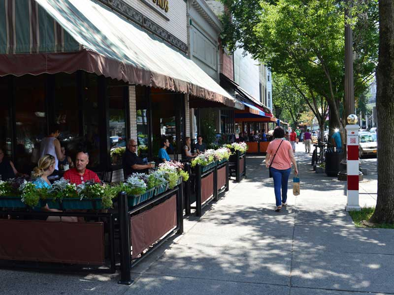Patio diners and people walking on Broadway in Saratoga Springs