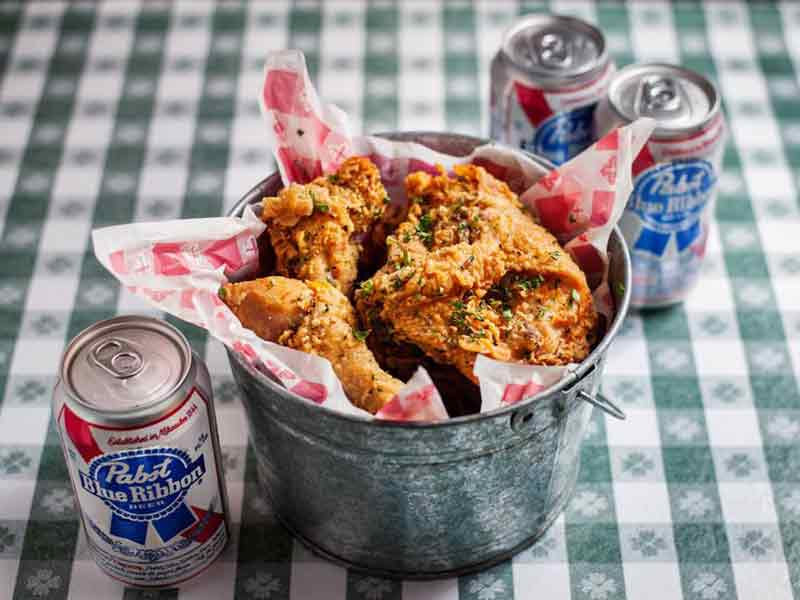 A bucket of Hattie's fried chicken on a table surrounded by canned beers