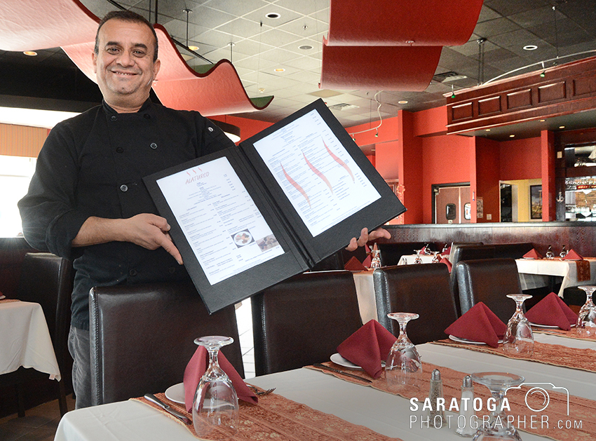Rauf Ziya, owner of Alaturco Mediterranean Grill in Clifton Park, displays his menu of largely Turkish dishes at the establishment he opened in Clifton Park Center on Clifton Country Road. ©2017 Saratoga Photographer.com