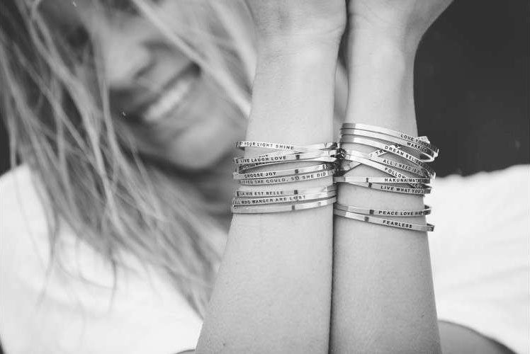 woman smiling showing off bracelets