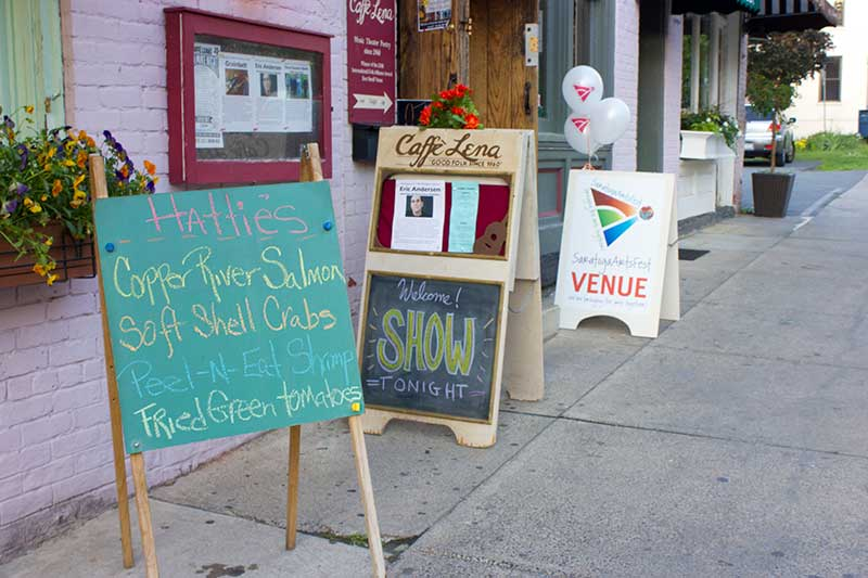 Sidewalk sign advertising Caffe Lena in Saratoga