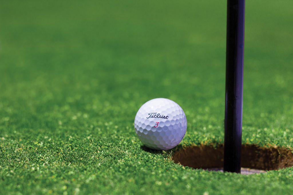 golf ball teeters on edge of hole