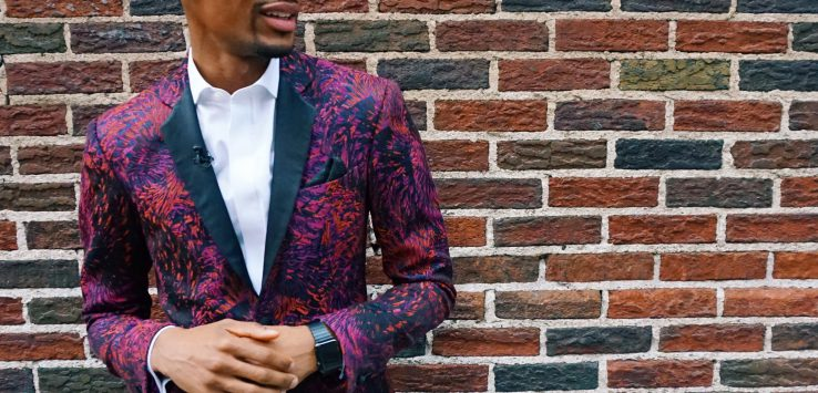 Jon Batiste in fireworks suite against brick wall
