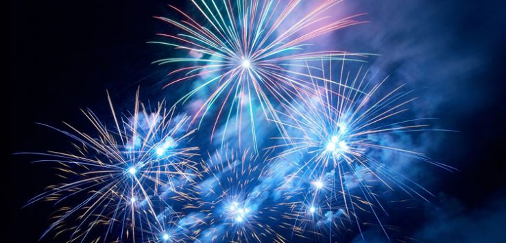 blue and reddish fireworks in the night sky
