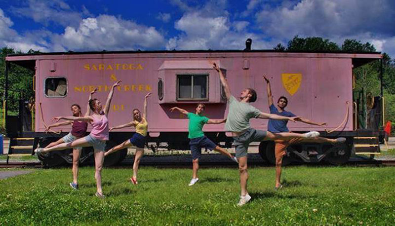 6 dancers posed in front of a pink trailer