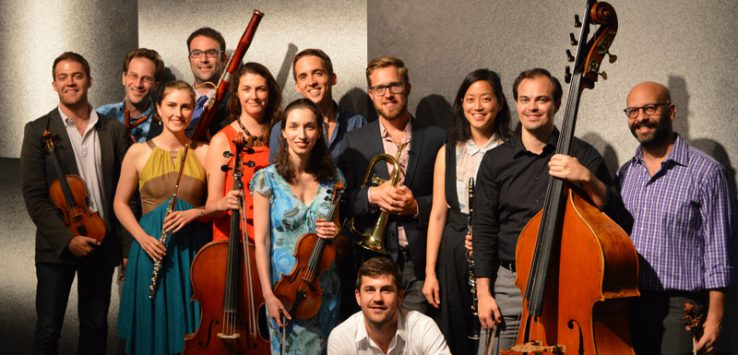 a very large ensemble of musicians gathered together
