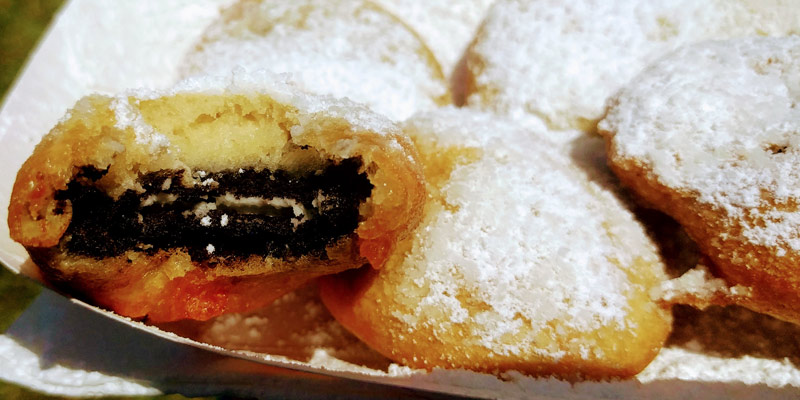 five deep fried Oreos with the one on the far left bitten into so you can see the inside