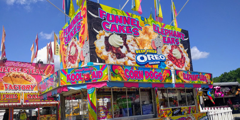 a food stand at the fair advertising funnel cakes and deep fried oreos