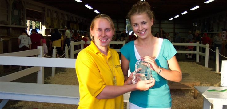 a woman at the fair presents a crystal plaque award to a young girl