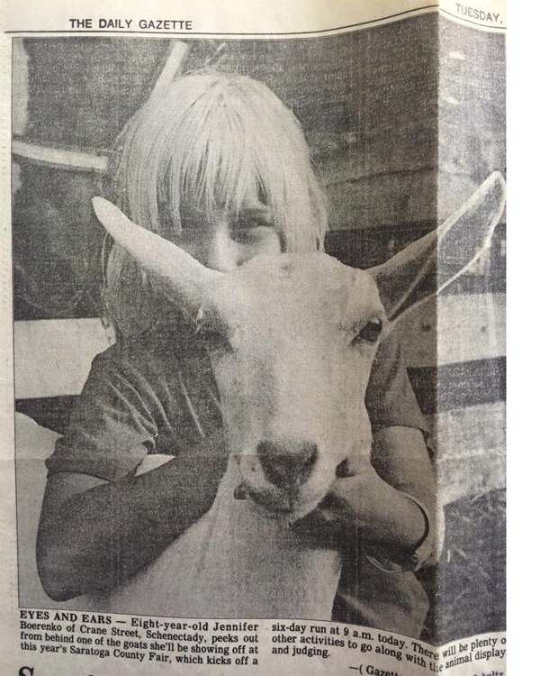 a black and white photo of an old newspaper with a young girl standing proudly behind a goat
