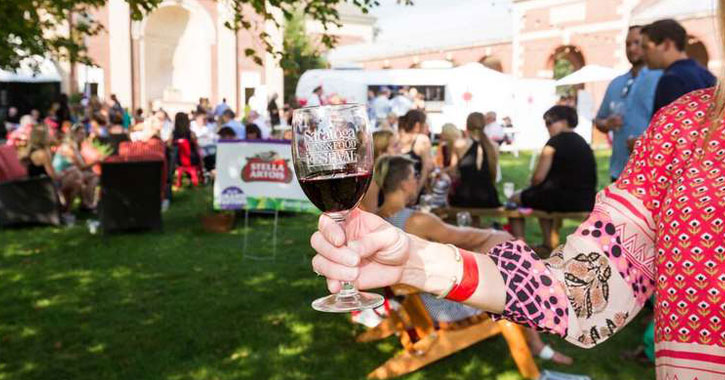 a hand holding up a glass that says Saratoga Wine and Food Festival