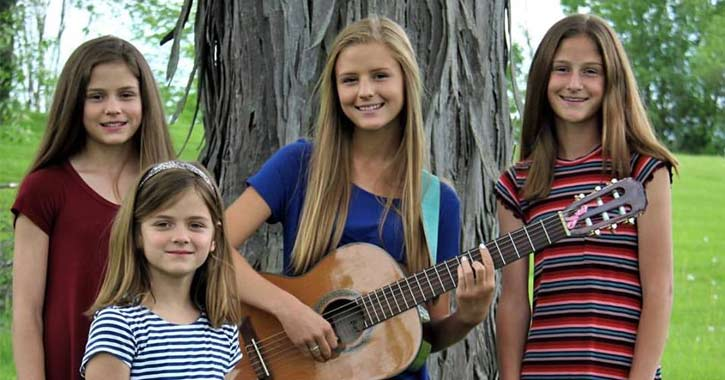 four girls posing by a tree, one with guitar