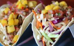 two colorful tacos in a little stand