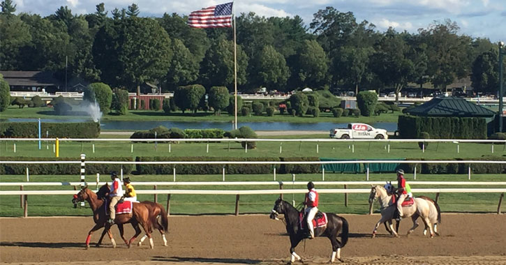 horses on the track with an American flag in the background