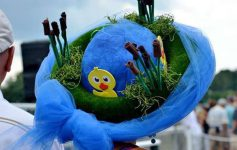 a blue hat on a woman's head with a little duck in it, looks like it's in a pond surrounded by grass