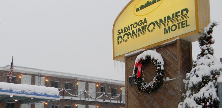 the Saratoga Downtowner sign in front of the motel, covered in snow