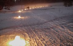 people snowshoeing by candlelight