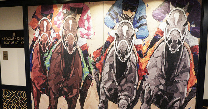 a horse racing mural on a wall