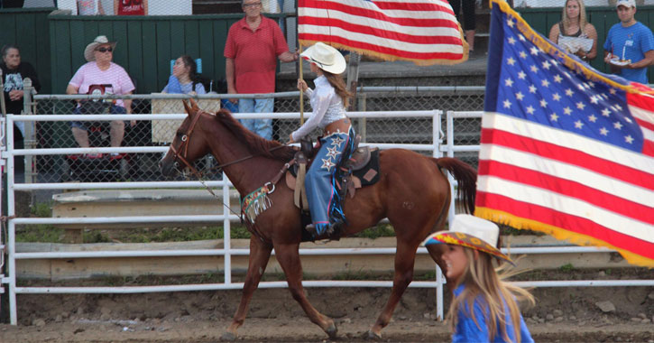 women riding horses in a ring with American flags