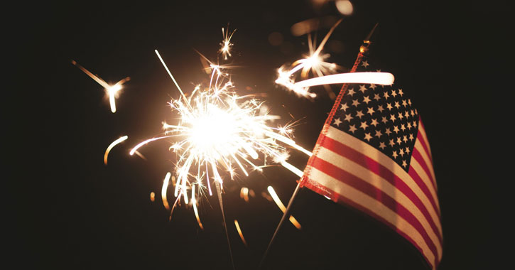 a small American flag waving next to a sparkler