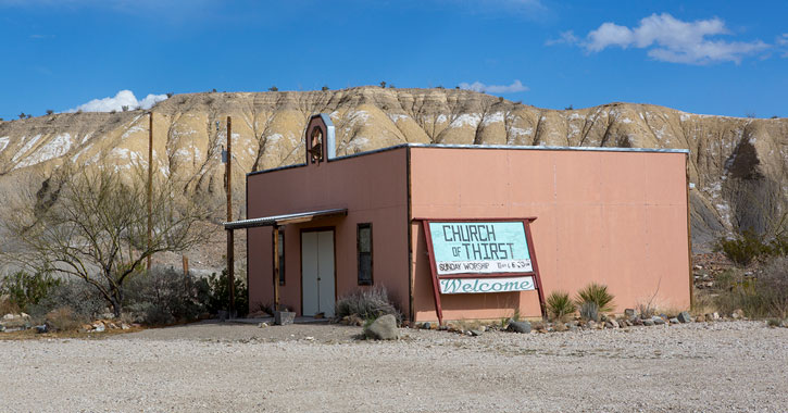 a small building in a dessert that says Church of Thirst