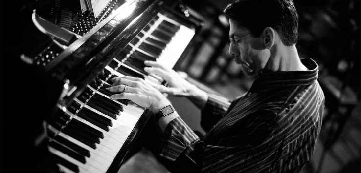 black and white photo of man at piano