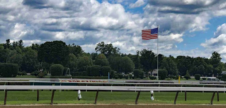 an american flag flying in the center of the saratoga race track