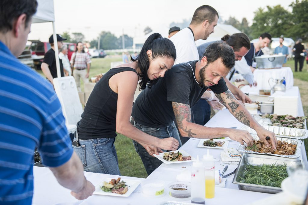 chef and helpers plating the feast