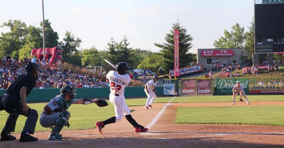 baseball players on field, one swinging a bat