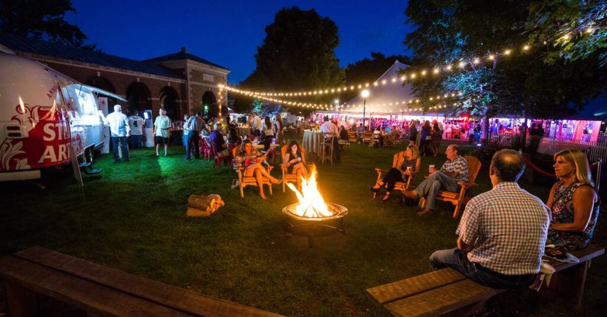 people sitting around a fire pit at the festival