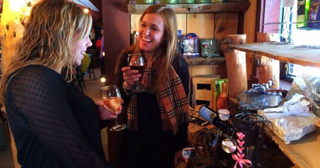 two women drinking wine in winery