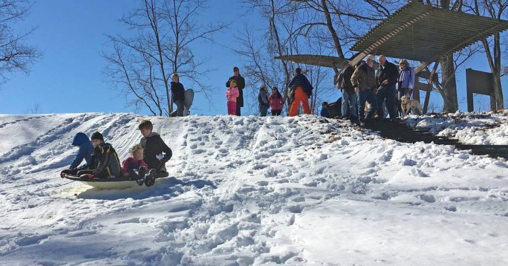 people saucer sledding on hill