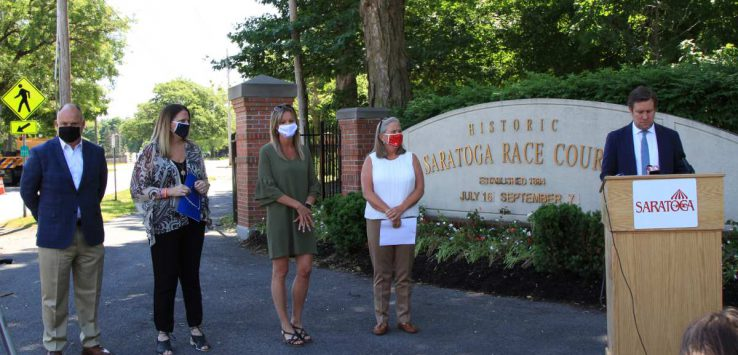 people standing near sign with face masks on