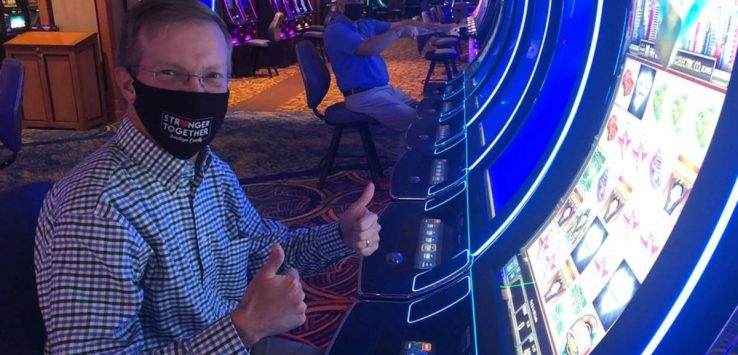 man wearing black mask at casino machine