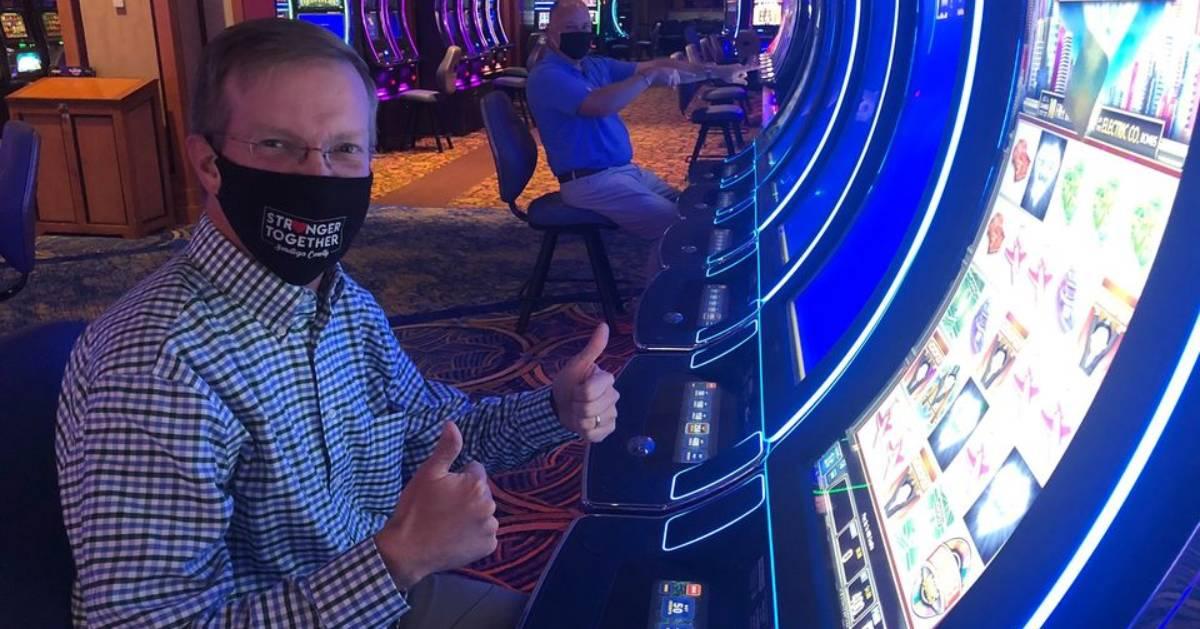 man wearing black mask at casino machine