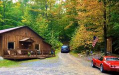 a rustic building in the woods near some cars