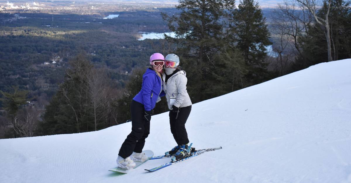 two women on snowy mountain, one with skis and one with a snowboard