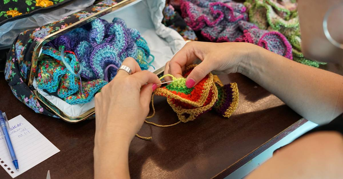 person making crochet piece