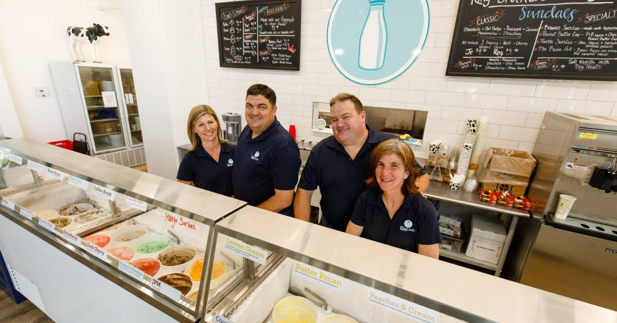 two men and two women behind counter of ice cream shop