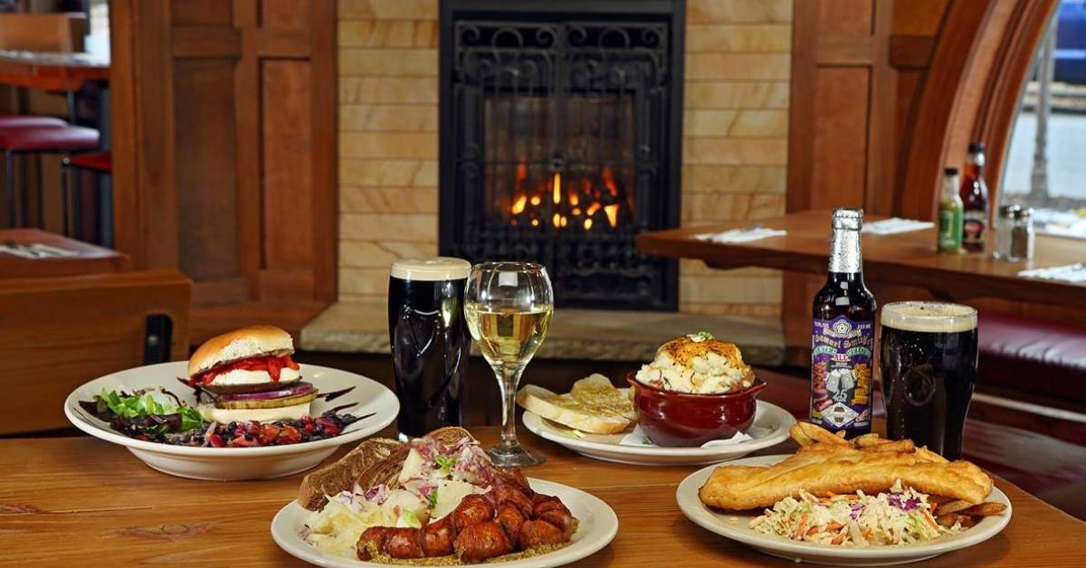 food and drinks on table in restaurant with fireplace on back wall