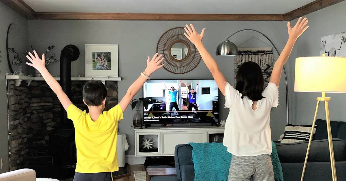 two people in a room following dance view on tv
