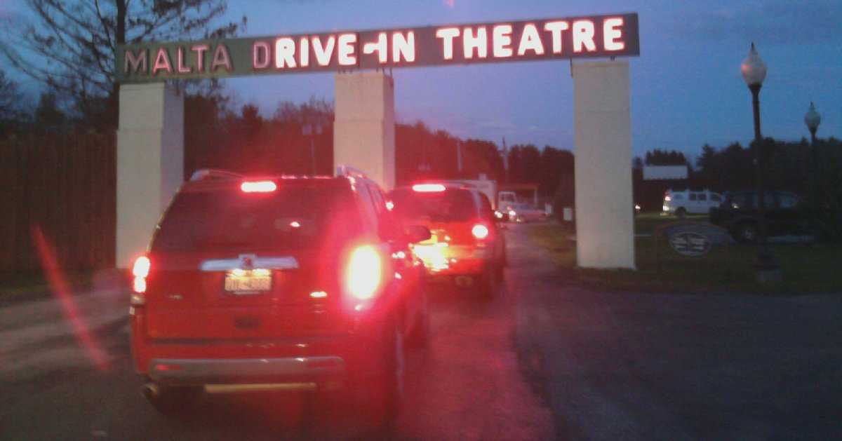 cars driving into a drive in theatre at night