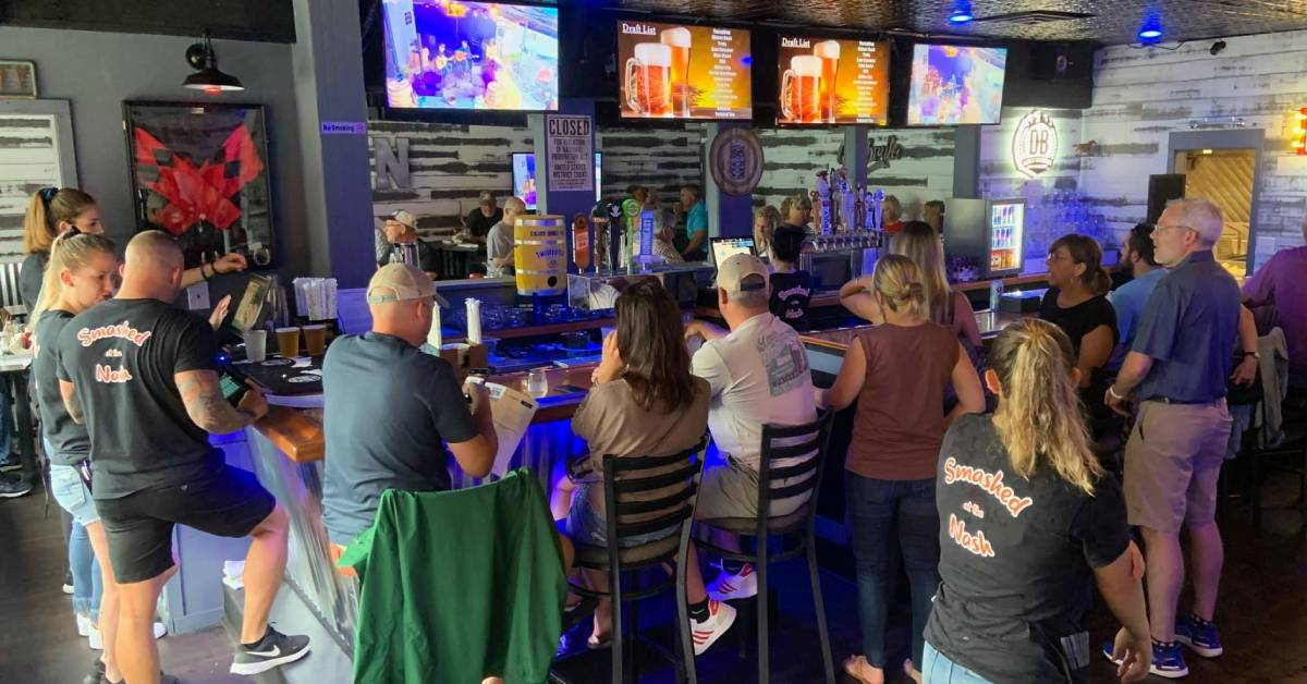 people inside a bar with tvs