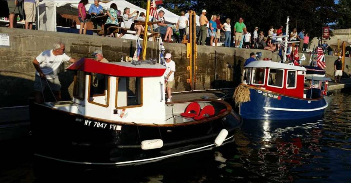 people standing near tugboats